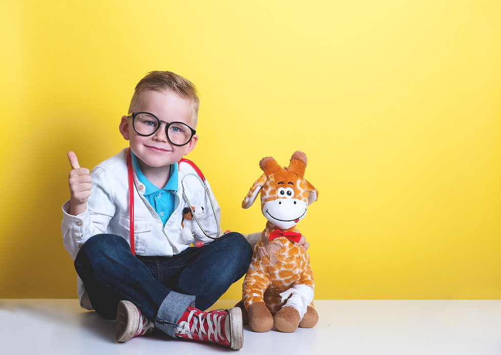 Child playing doctor with toy animal gir