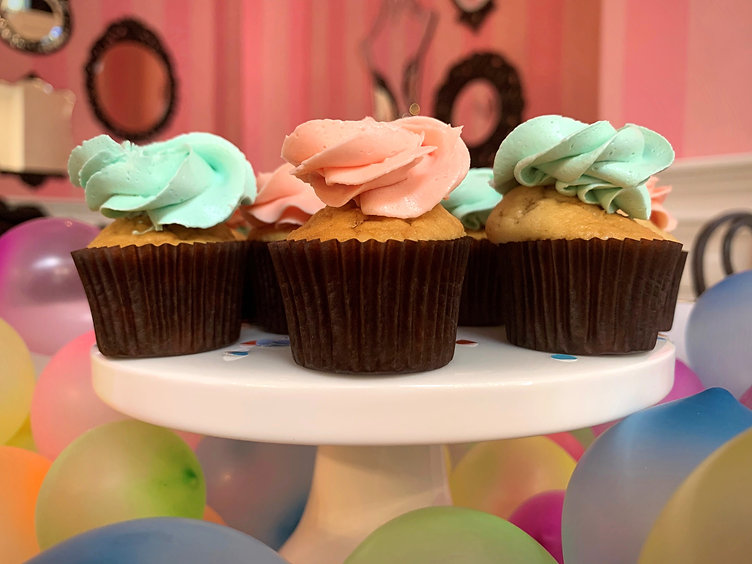 Party scene with platter of babycakes featuring colourful frosting