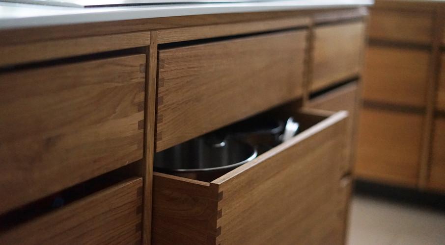 Egetræskøkken med fingertappede skuffer og Corian bordplade