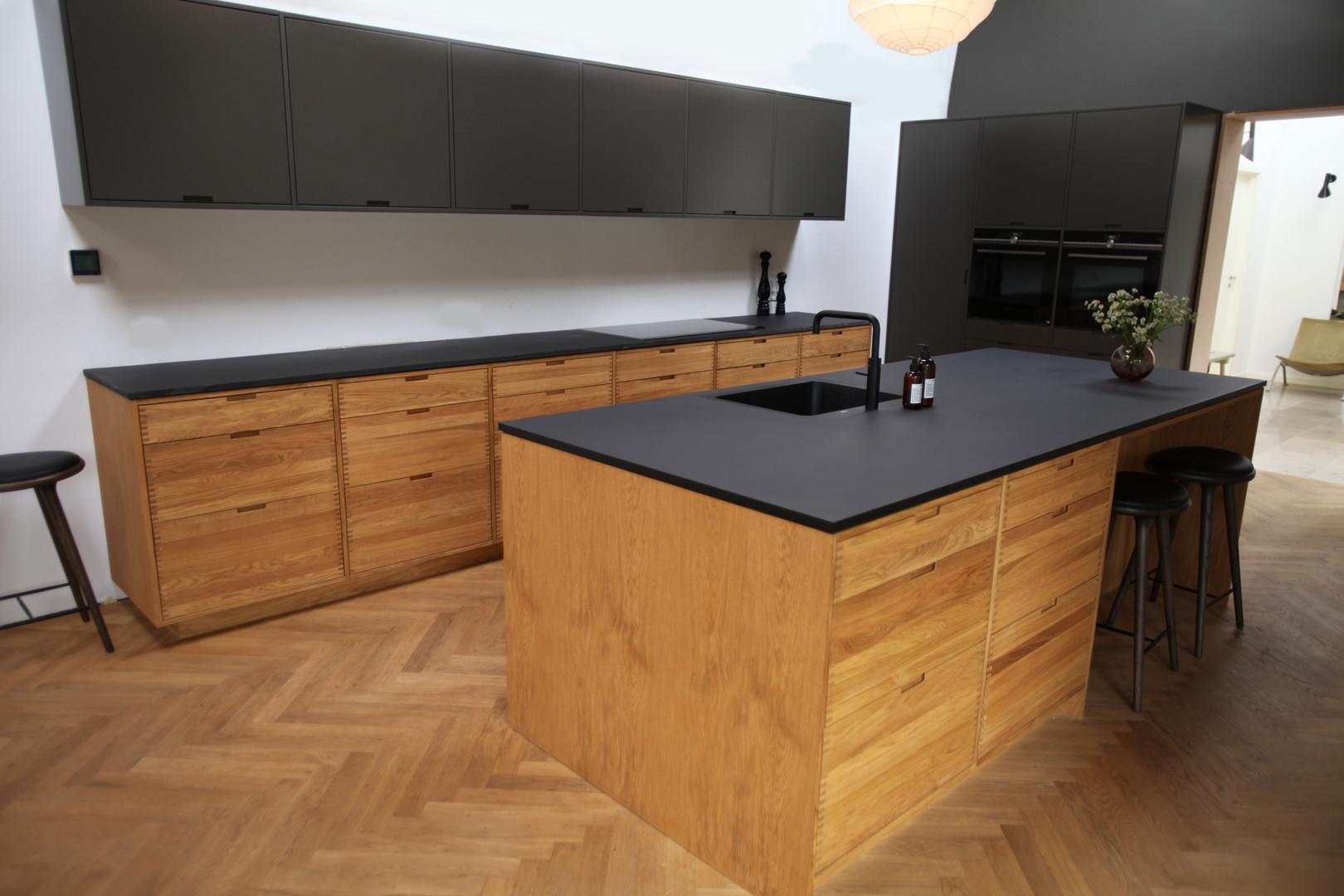 Køkken i egetræ med massive fingertappede skuffer og sortmalede skabe