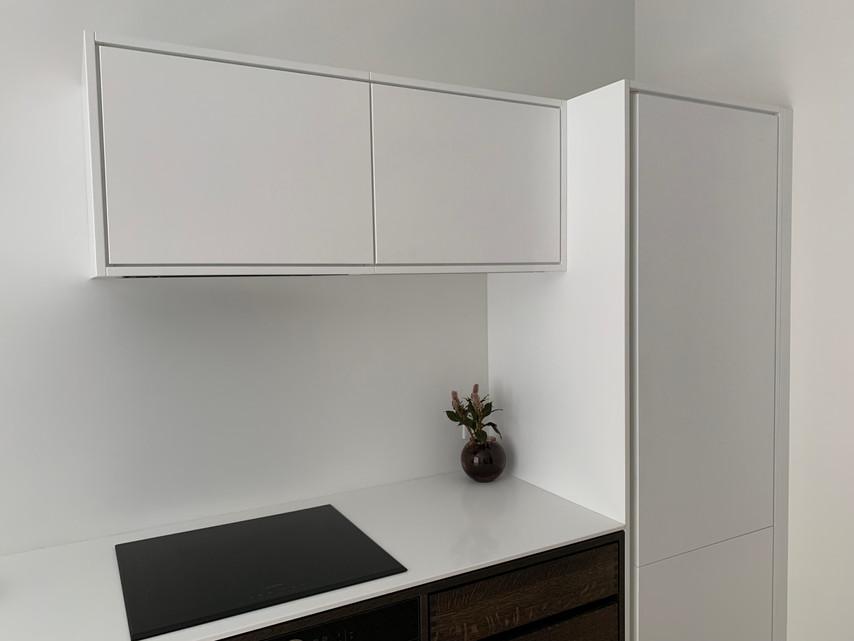 Køkken i mørkolieret egetræ med hvide skabslåger