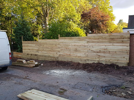 Rustic 6 inch slatted fence with retaining sleepers installation