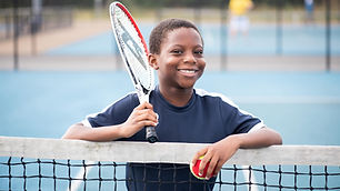 Boy at tennis net on outdoor tennis court