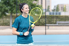 Lady playing tennis on outdoor court
