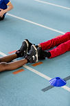 Image of two sets of legs lying down on athletics track with soles of feet in trainers touching