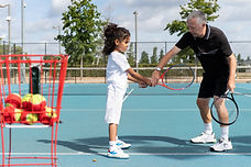 Child receiving tennis coaching