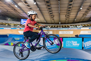 Child cycling on indoor pump track