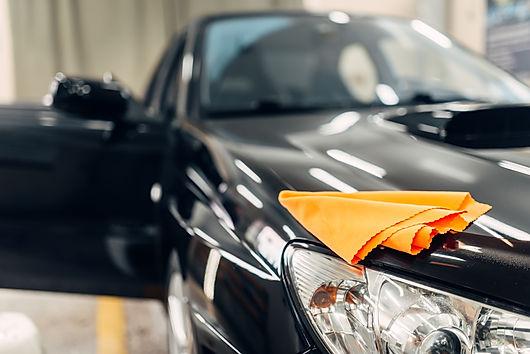 rag-on-the-hood-of-clean-car-on-carwash-