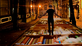 image of a person with headphones on walking a magical street paved with books.