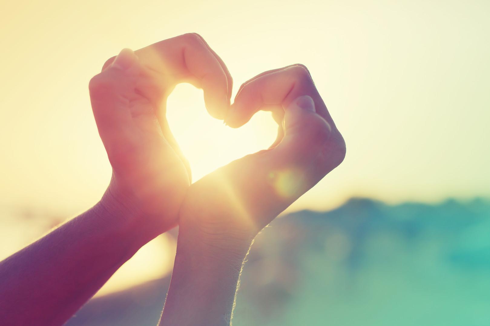 hands in heart shape framing setting su