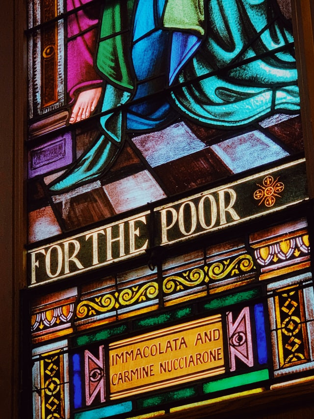 """A portion of a stained glass window depicting blue and green robes on a black-and-white checkerboard floor. The caption reads """"For the Poor"""" and the dedication says """"Immacolata and Carmine Nucciarone""""."""