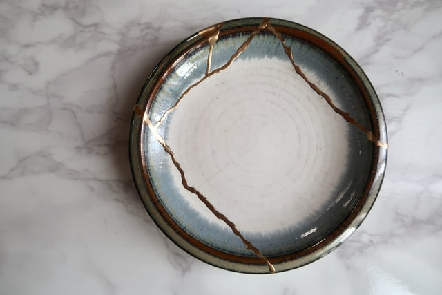 A stoneare bowl glazed in white and blue which was broken into five pieces has been repaired with gold to be whole again.