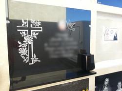 Lapida con cruz grabada y flores