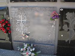 Lapida con cruz tallada y flores