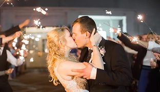 Bride and groom kissing in foreground. Sparkler celebration behind them in background. Kentucky wedding.