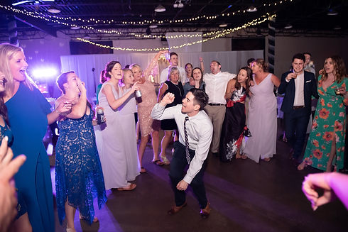A group on the dancefloor singing and dancing at Kentucky wedding by RipTide Productions.