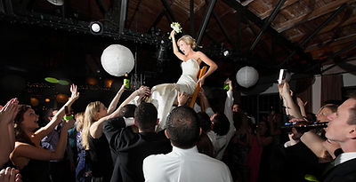 Bride raised in chair above crowd at RipTide Productions event in Kentucky.
