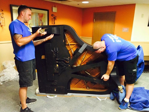 Mike Holdiay and Josh Wyno moving a piano for their client