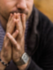 close up of man with hands together holding chin