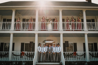 bridesmaids and groomsmen front of house