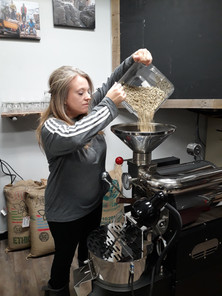 Raw beans being poured into the hopper.