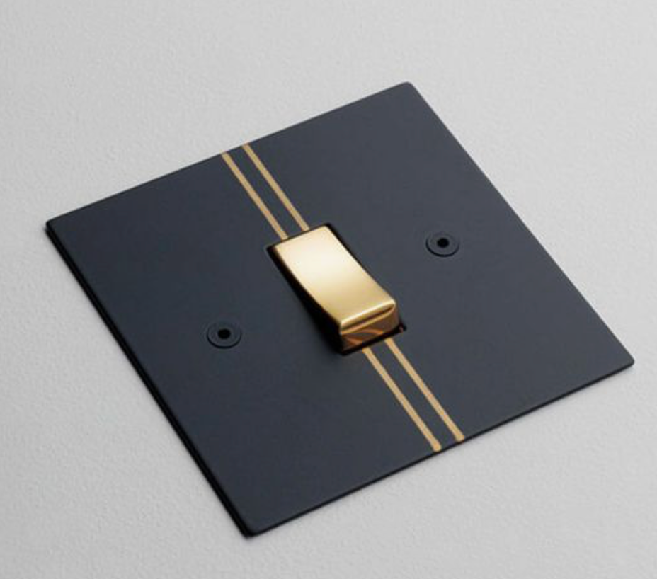 Kelly Hoppen designed light switches. Matt black and gold pinstripe
