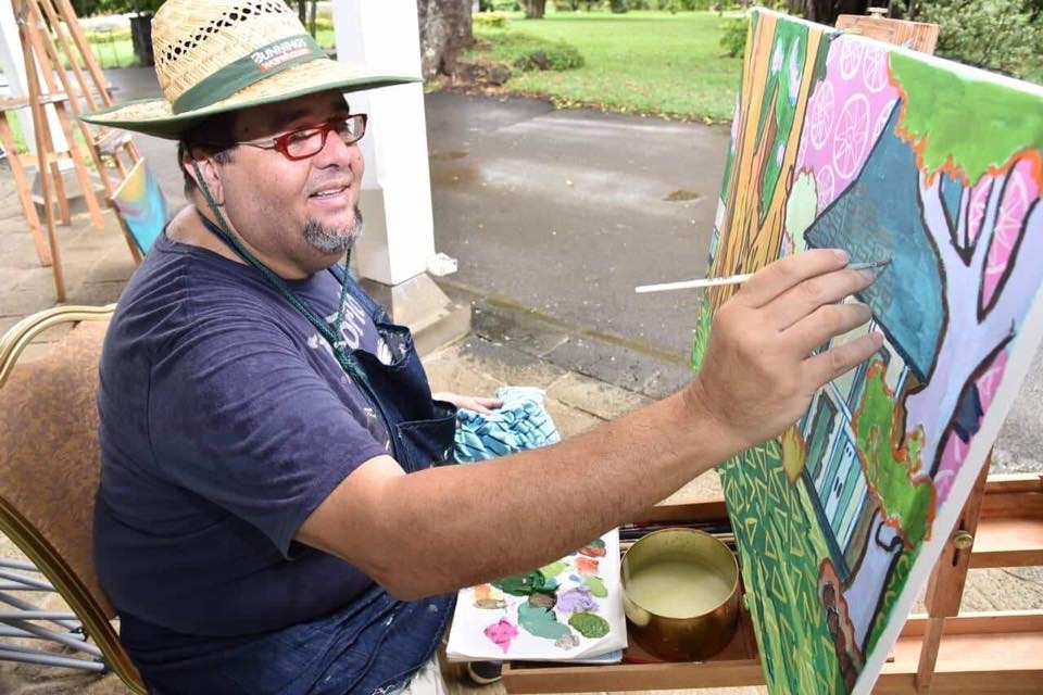 Mauritian artist Pascal Lagesse painting on site at Pamplemousses gardens