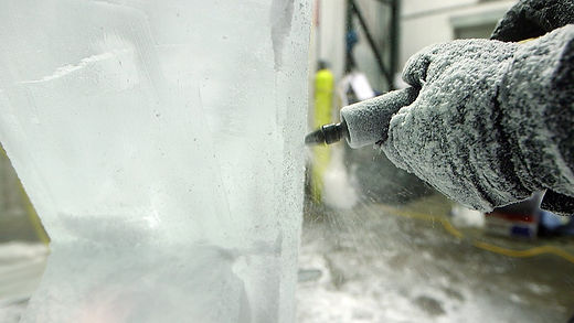 A close-up of O'Malley using a grinding tool to add some detail work into the ice sculpture
