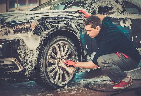 Man worker washing car's alloy wheels on
