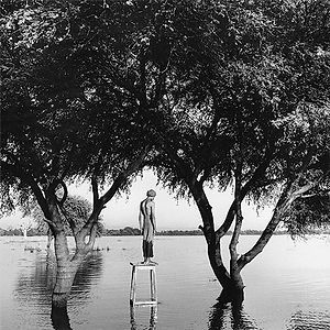 young man standing on tall stool in the river in Burma/Myanmar