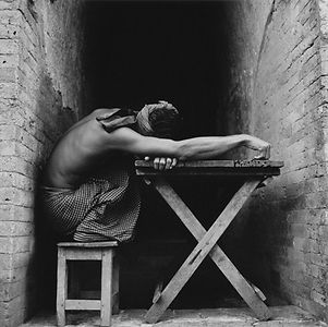 shirtless man crouching on rough wooden stool and table in Burma/Myanmar