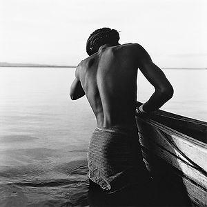 strong, muscular, shirtless man pushing a wooden boat in Burma/Myanmar