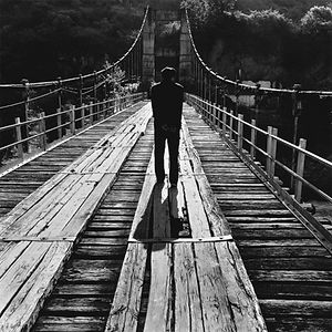 Man on old, wooden bridge with Mao star.