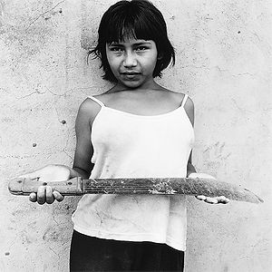 village girl holding worn machete near Rio Cuara, Venezuela