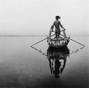 boatman with long crossed oars and reflection in Burma/Myanmar