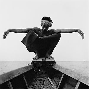 man wit outstretched arms sitting relaxed in the front of a boat in Burma/Myanmar