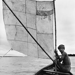 young man on small boat with big sail in Burma/Myanmar