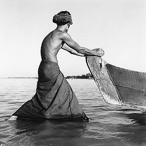 a man pulling a wooden boat in Burma/Myanmar