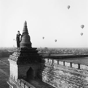 girl standing on a pagoda with hot air balloons in the background in Burma/Myanmar