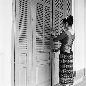 young woman is traditional Lao/Laos clothng in front of french doors in Luang Prabang