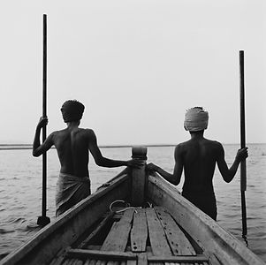 two young men holding long oars by their wooden boat in Burma/Myanmar