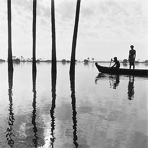 two men gliding quietly in a wooden boat through reflected palm trees in Burma/Myanmar