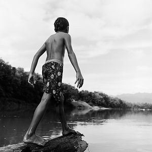 young boy about to dive into the Nam Khan River near Luang Prabang, Lao/Laos
