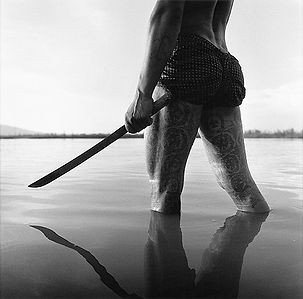 mans's muscular, tattooed thighs and long knife in the river in Burma/Myanmar