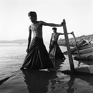 two men in submerged, sunken wooden boat in Buma/Myanmar