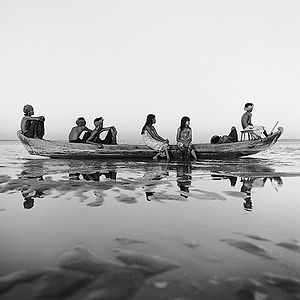 group of children on an adventure in a long, wooden boat in Buma/Myanmar