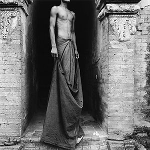 lean, tall, shirtless man standing in the ruins in Burma/Myanmar