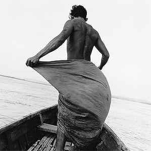 dynamic, muscular man standing in a wooden boat in Burma/Myanmar
