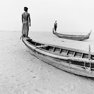 two men standing on the bow of wooden boats in the sand in Burma/Myanmar