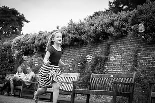 Black and white documentary lifestyle portrait photoshoot of a young girl chasing bubbles in the gardens of Non Such Park